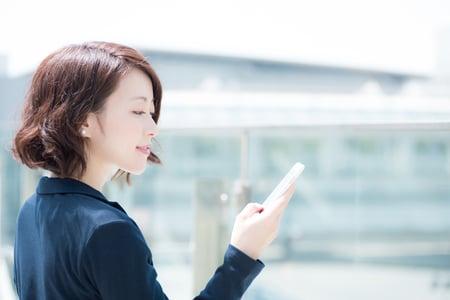 スマートフォンでWeb会議する女性